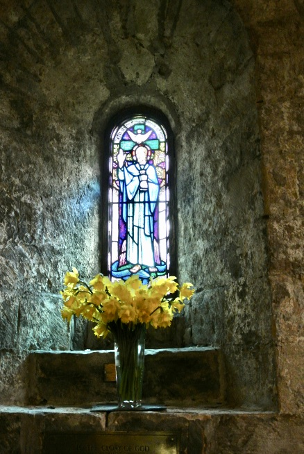 A vase with yellow flowers and a stained glass window.