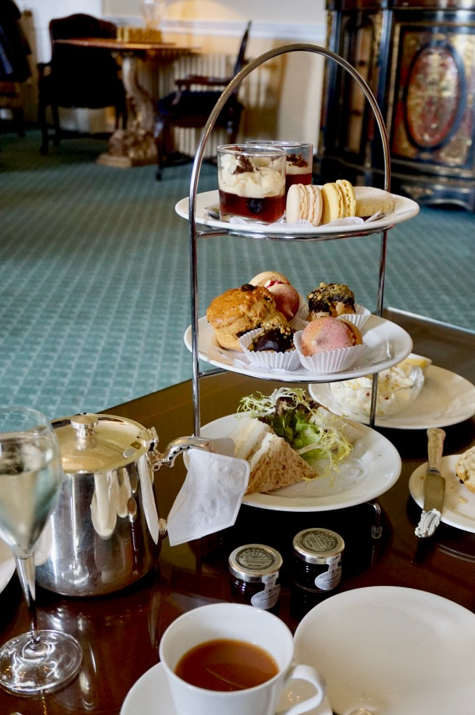 Tiered trays of afternoon tea foods.  A silver teapot and cup of tea.