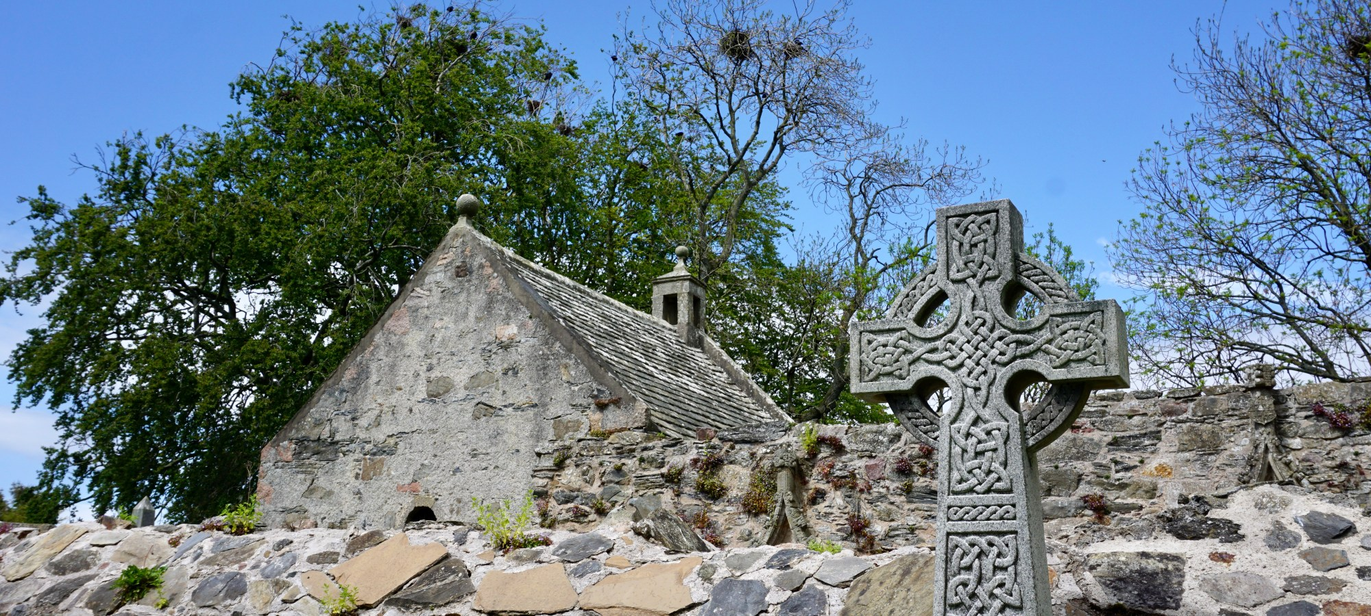 A celtic cross in front of a stone wall and stone building.