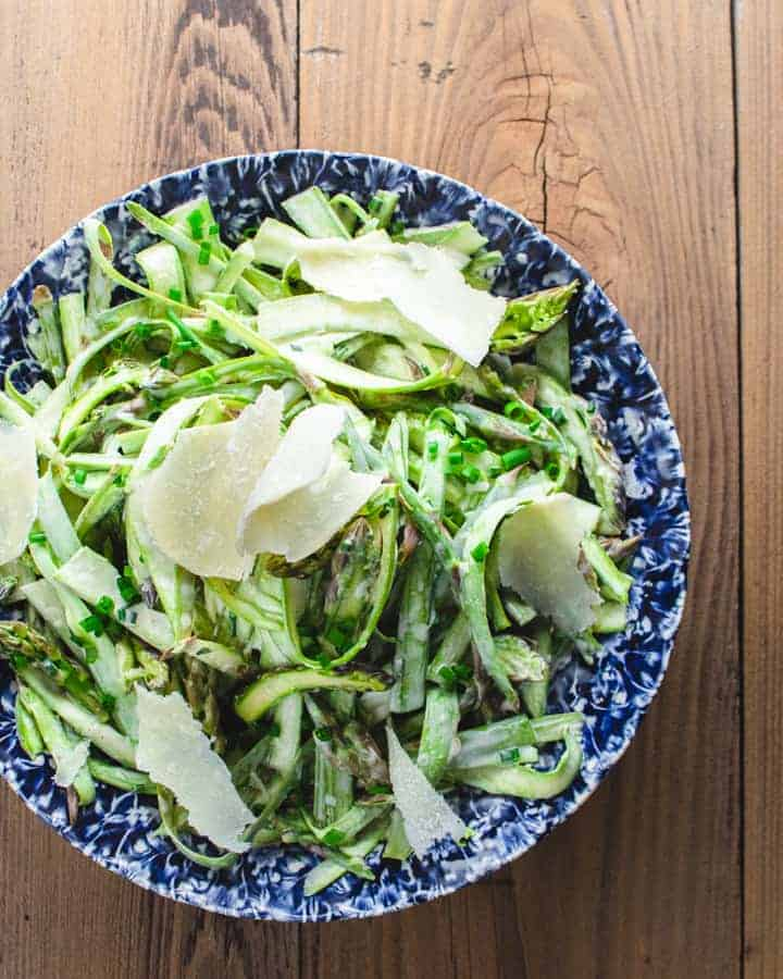 Creamy shaved asparagus salad with creamy Parmesan dressing on a blue plate