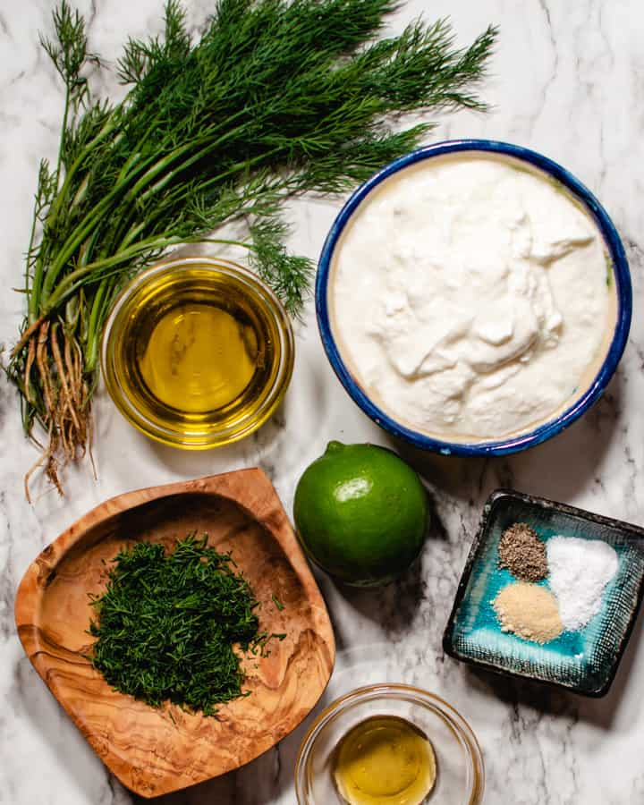 Ingredients for creamy dill dressing on a marble background