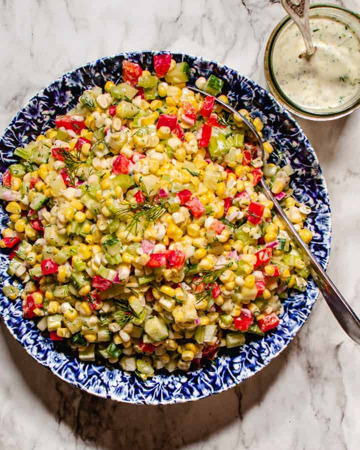 Corn salad in blue and white bowl on marble background with jar of creamy dill dressing