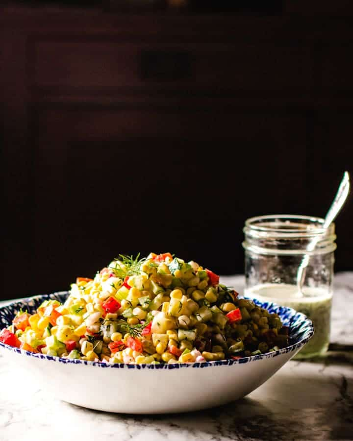 Corn salad in a blue and white bowl, black background and jar of creamy dill dressing