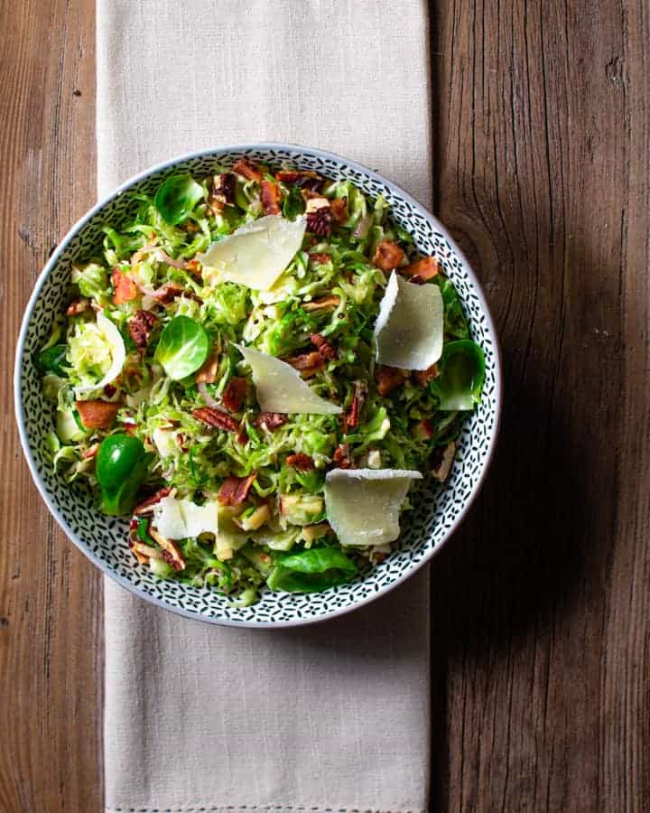 Brussels sprouts bacon and apple slaw in a round bowl on top of a cloth napkin