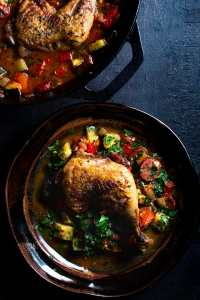 spanish chicken bake. single serving on dark pottery plate. cast iron skillet on the side with the rest of the dish.