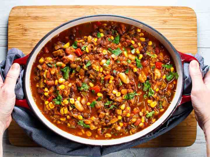 oval pot of vegetarian chili being held by 2 hands with blue towel