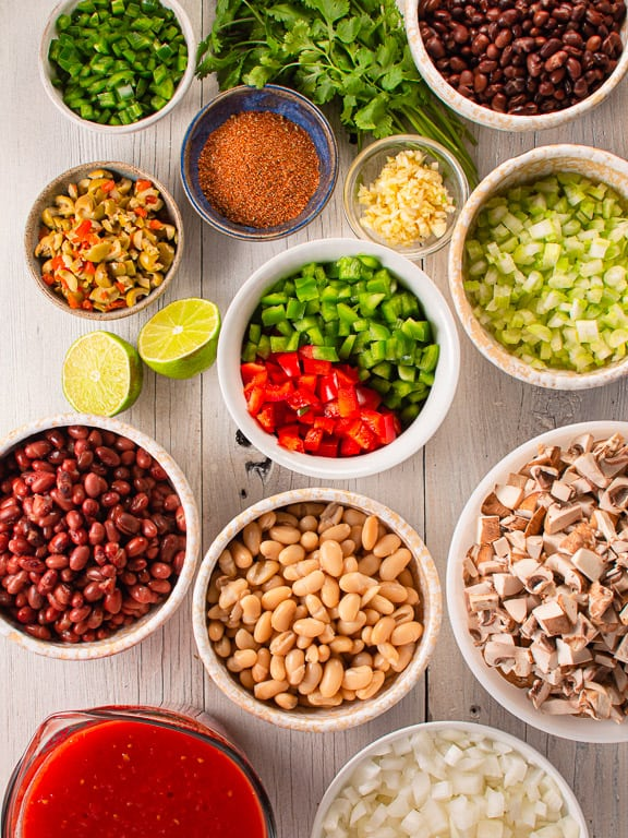 Prepped ingredients for vegetarian chili in white bowls
