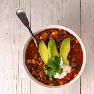 single bowl of vegetarian 3 bean chili garnished with sliced avocado, cilantro and sour cream