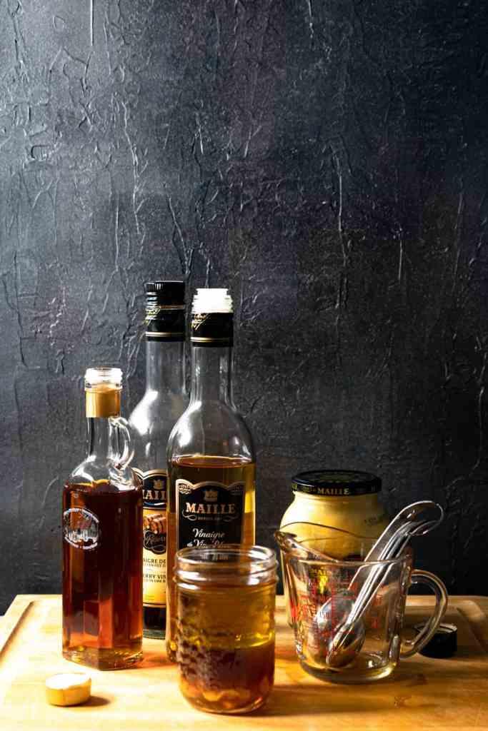 ingredients for maple dijon vinaigrette on wood board