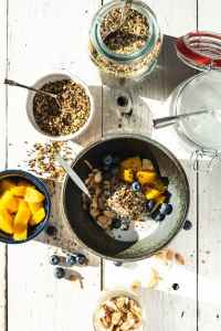 Killer grain & seed cereal plus dishes of toppings on white wood background
