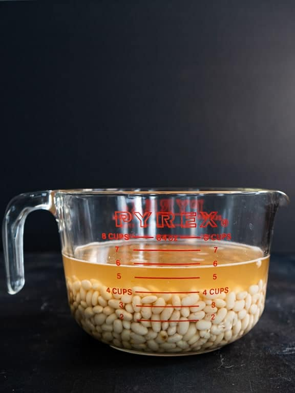 Cooked navy beans with cooking liquid, glass measuring cup