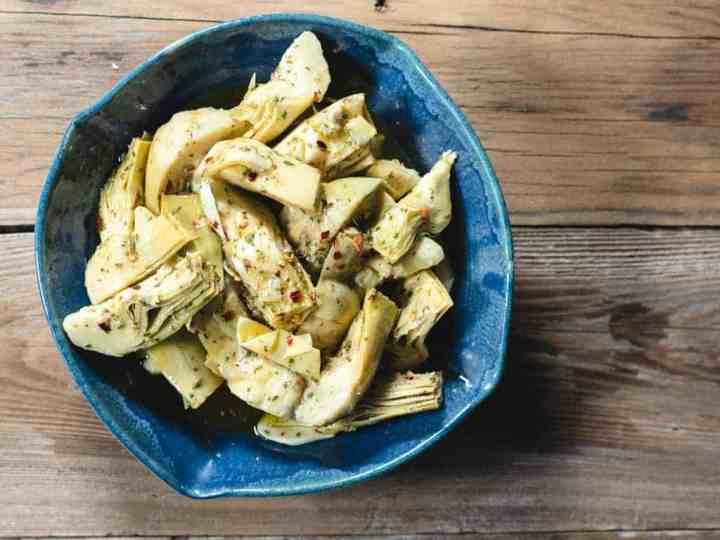 marinated artichoke hearts in blue ceramic bowl on wood background