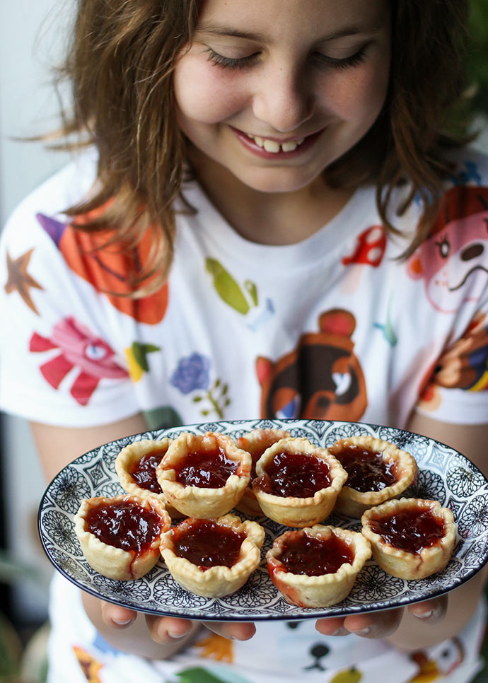 Girl holding plate of jam tarts