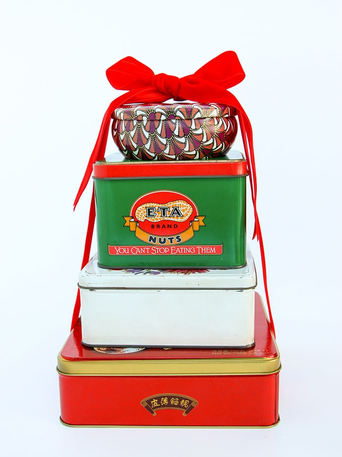 Vintage tins stacked with a bow