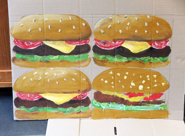 giant painted hamburgers on cardboard.