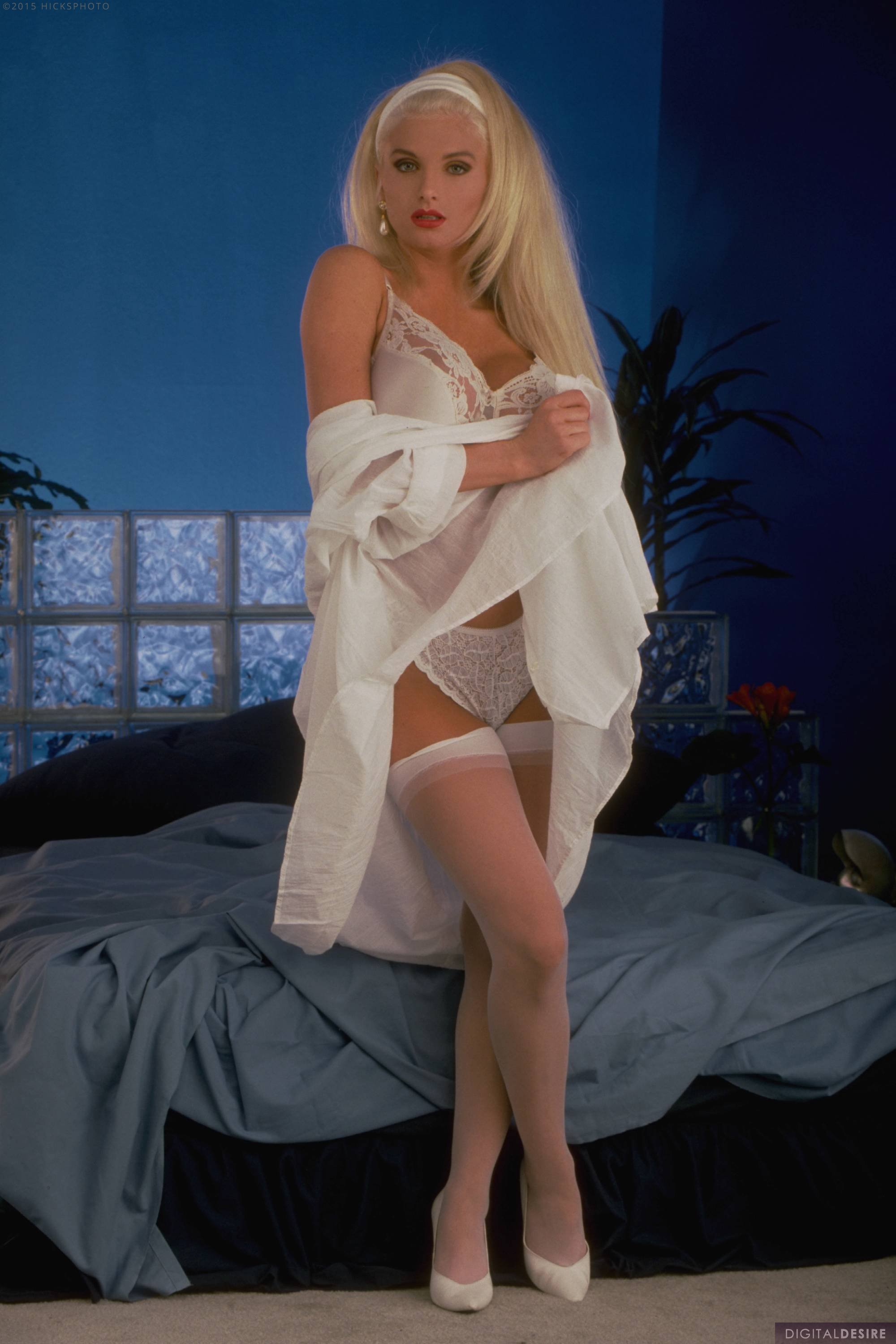 Young Taylor Wane in white stockings and heels posing on bed.