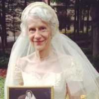 This grandma posed in her wedding dress holding her picture that was taken from 1953