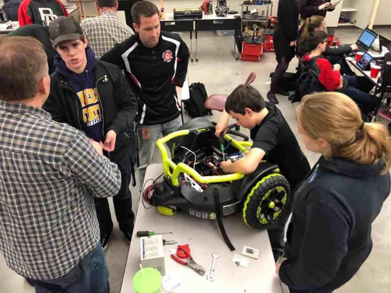 Farmington High School freshman Alex Treakle, working on the car, said he was glad he could help