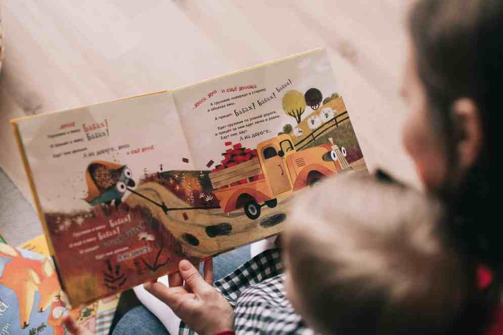 Toddler reading printed book with adult