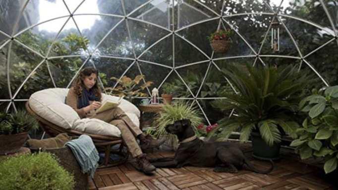 A woman reading inside a garden igloo