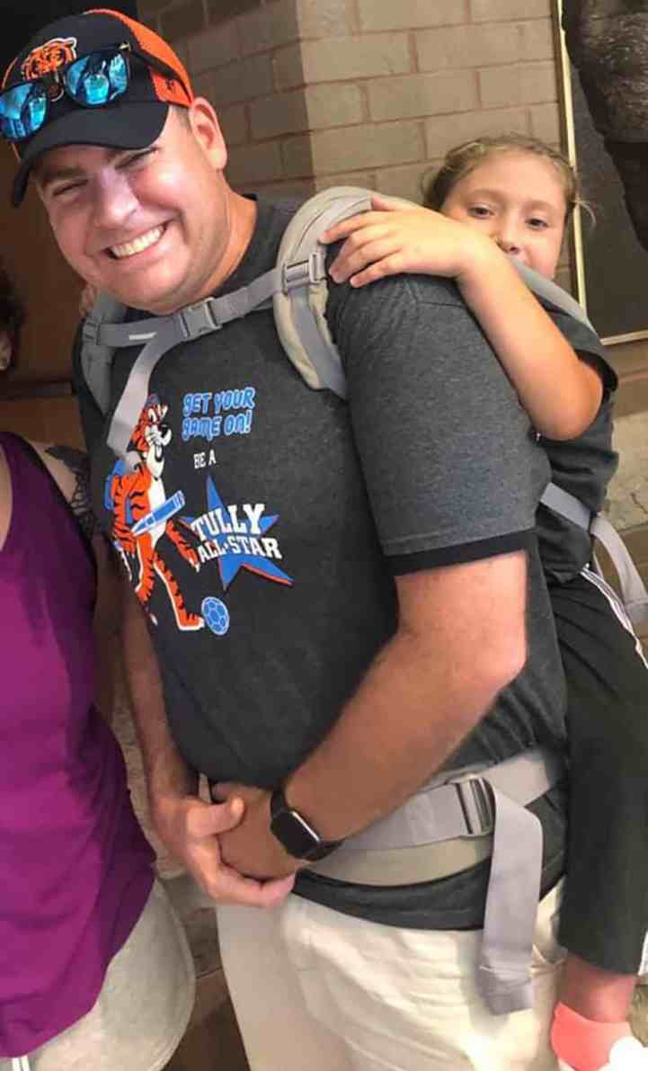 elementary school teacher carries student