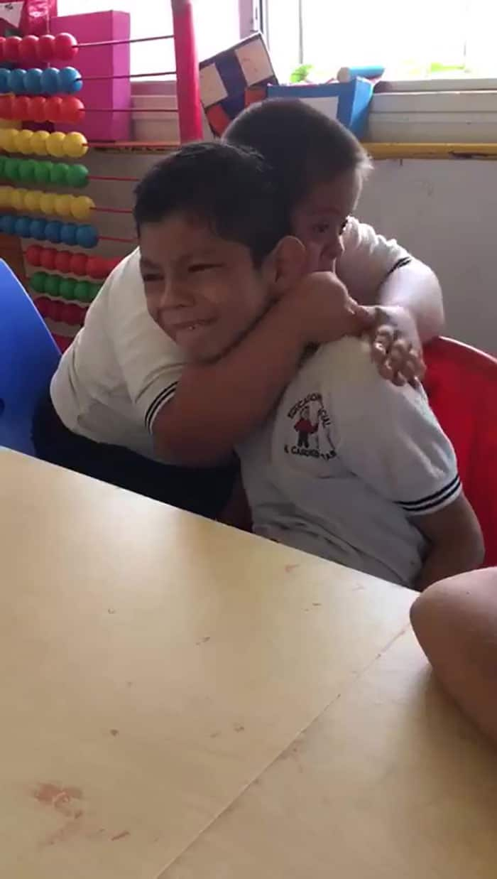 Boy with autism getting comforted by classmate in an elementary school.
