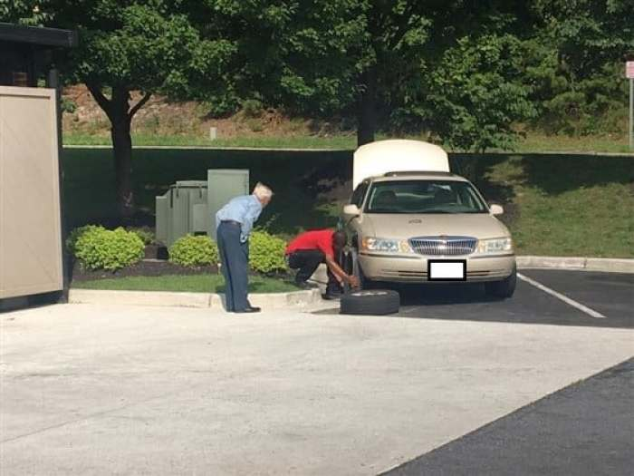 Daryl Howard changing Mr. Lee's flat tire
