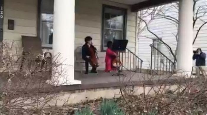 Two children playing cello instrument