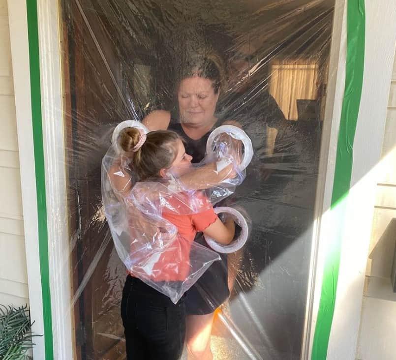 Hugging her grandkid through a plastic curtain.