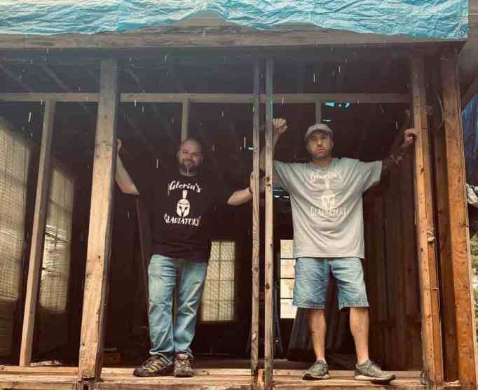 Two men standing on an unfinished section of a home they're renovating