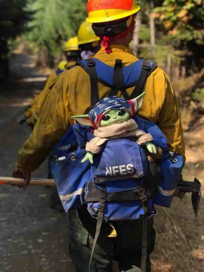 Baby Yoda in a backpack of a firefighter