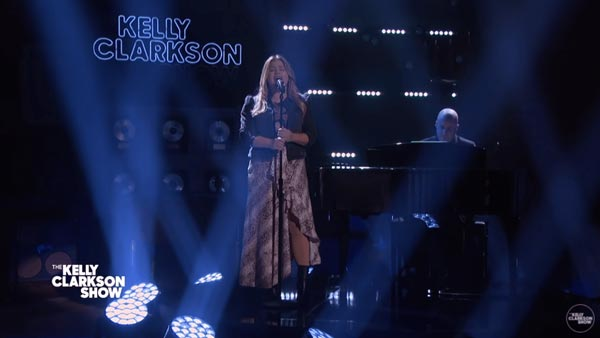 Kelly singing with piano in the background.