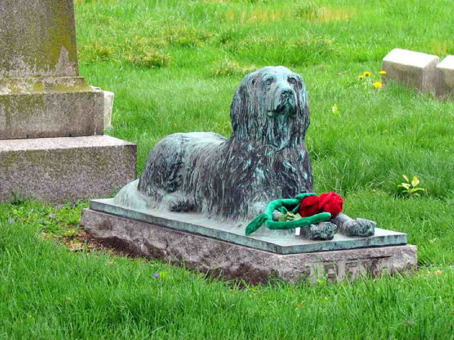 A statue of a dog at Green-Wood Cemetery that often gets toys
