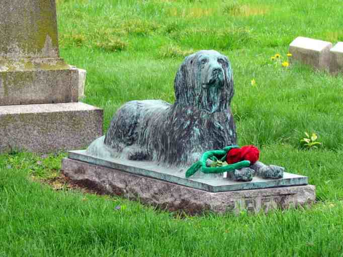 A statue of a dog at Green-Wood Cemetery that often gets toys and sticks.