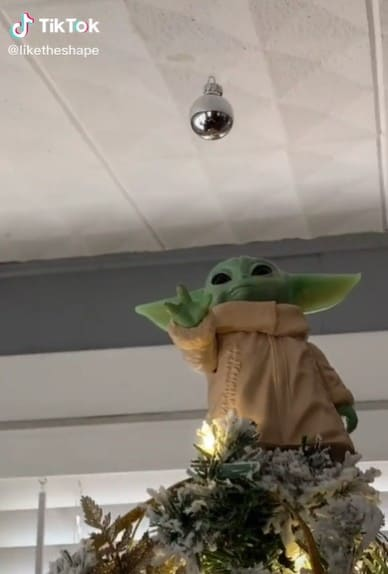 A Baby Yoda action figure as a Christmas tree topper