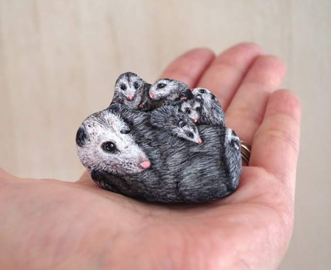 An image of an opossum family painted on a stone by Akie Nakata