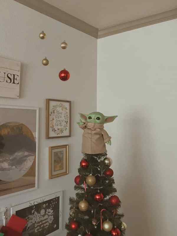Baby Yoda Christmas tree topper reaching for multiple baubles