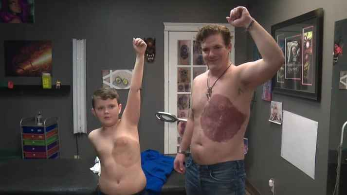 dad and son with identical tattoos raising their arms