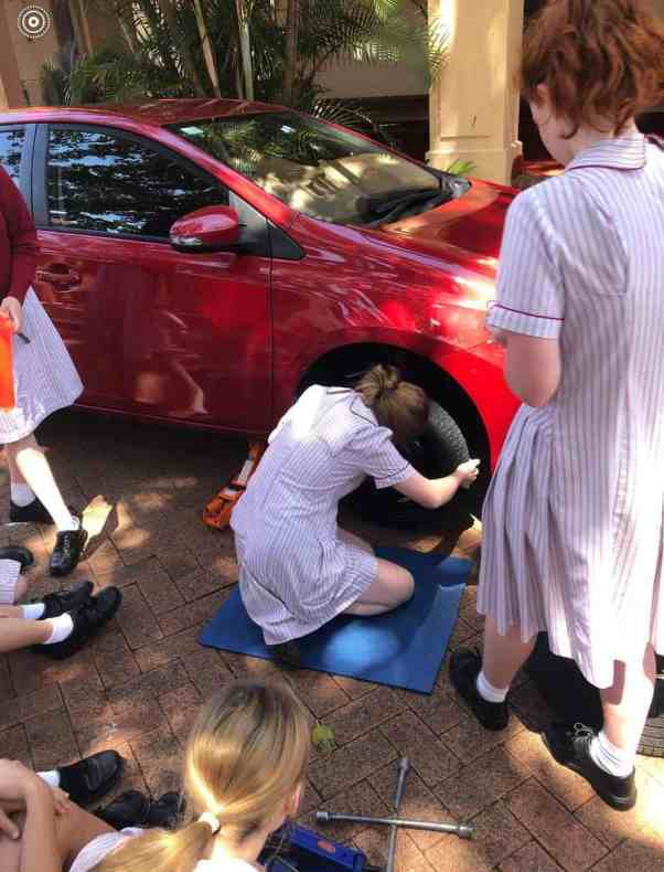 A teenage girl attempting to change a tire during a basic car maintenance workshop