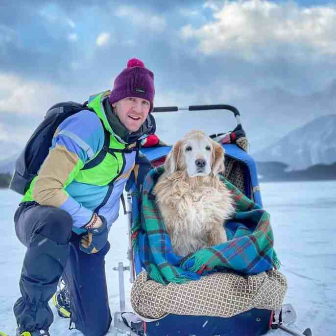 A man with his Golden Retriever sitting on a makeshift chariot