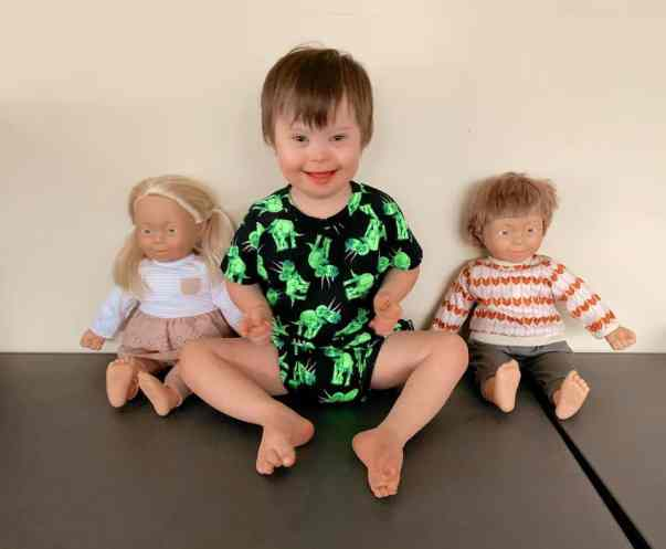Elijah posing with the Baby Charlie with Down Syndrome dolls from Kmart