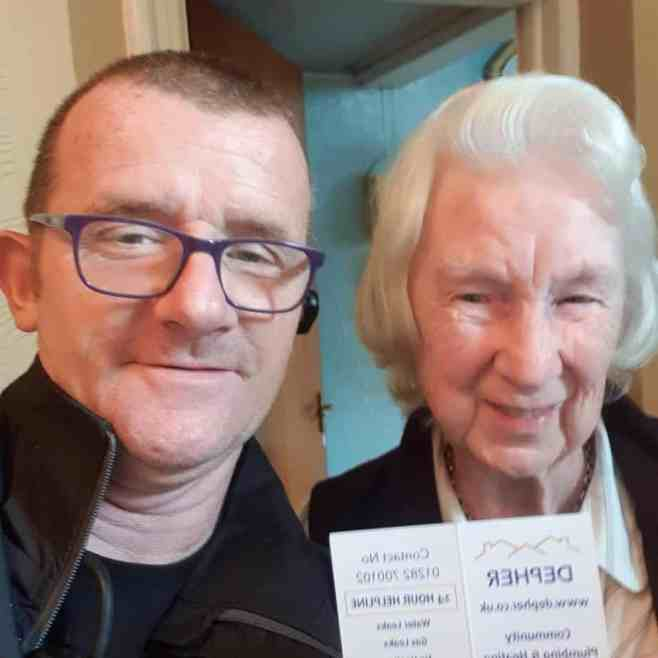 James Anderson with an elderly woman holding a plumbing service receipt