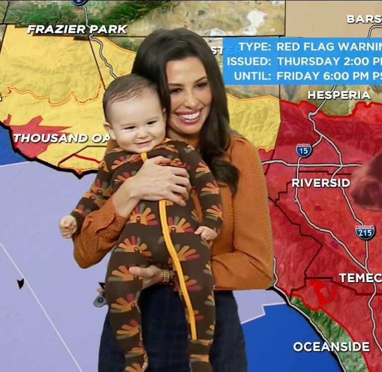 A female meteorologist carrying her infant son during a live broadcast