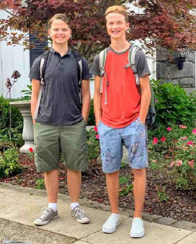 Two teenage boys wearing backpacks and standing beside each other