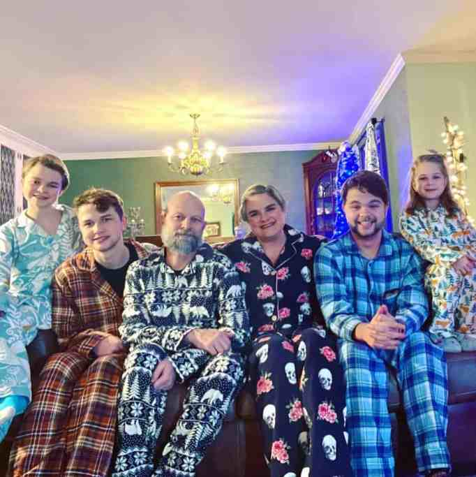 A family wearing pajamas sitting on a couch