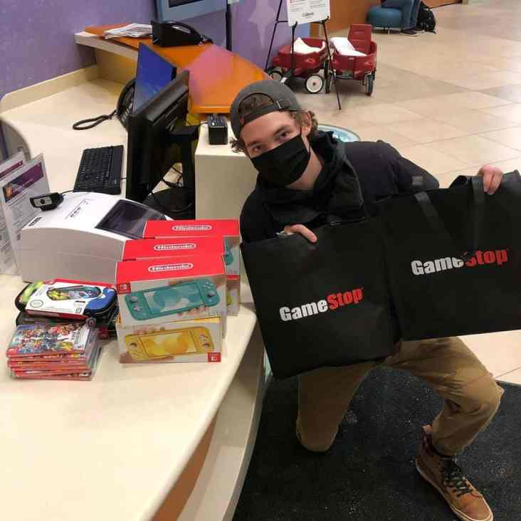 Hunter Kahn with the GameStop merchandise he will donate to Children's Minnesota hospital