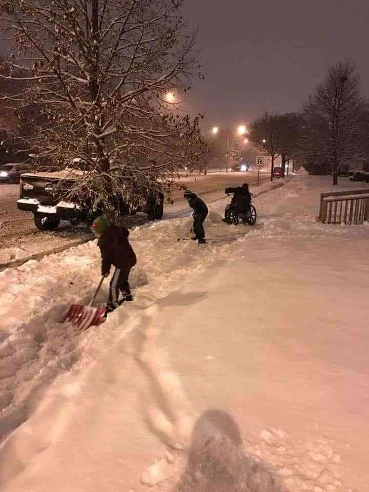 Three people shoveling snow off a property