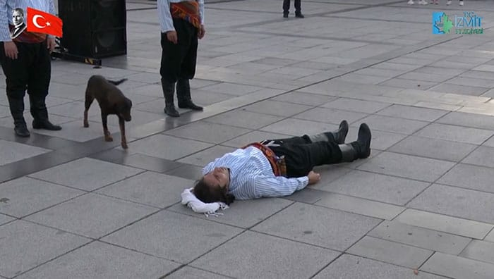 A stray dog approaching a man lying on the ground