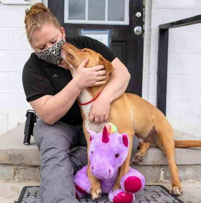 Officer Samantha Lane hugging Sisu the dog