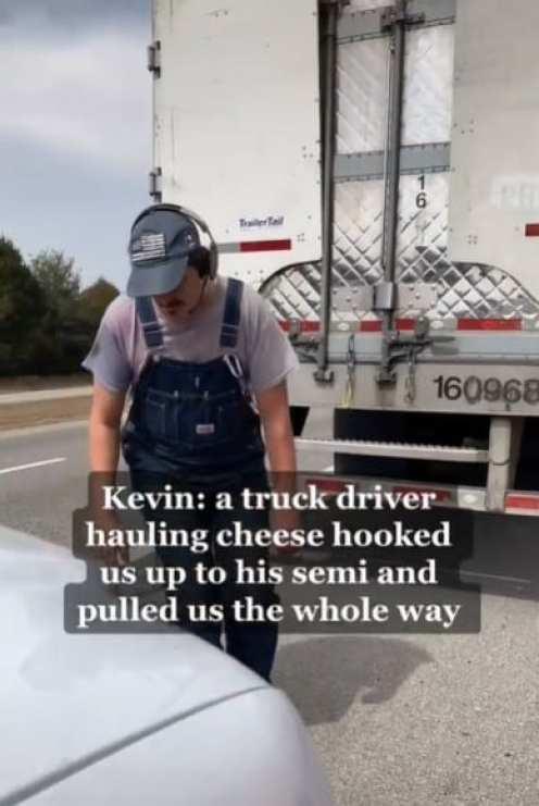 Водитель грузовика помогает семье, у которой кончился бензин на обочине дороги.
